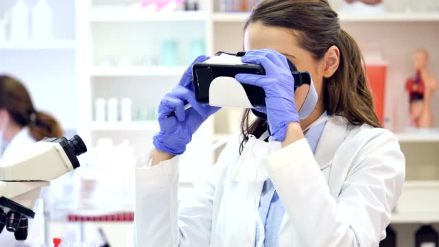 Young scientist uses virtual reality headset while conducting research video