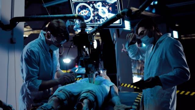 vídeos y material grabado en eventos de stock de los jóvenes científicos llevan a cabo la operación de la existencia alienígena con la ayuda de instrumentos y equipos quirúrgicos. alien yace en el laboratorio de la nave espacial. - autopsia