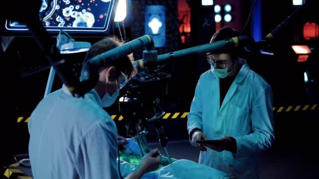 vídeos y material grabado en eventos de stock de los jóvenes científicos hacen una autopsia de un extraterrestre espacial. puedes ver las entrañas del cuerpo de un alienígena. la autopsia se realiza utilizando instrumentos quirúrgicos y equipos. - autopsia