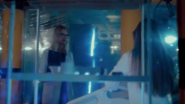 stockvideo's en b-roll-footage met jonge wetenschappers meisjes praten over plannen voor het uitvoeren van experimenten. zicht door de transparante wanden van het science lab. - ventilator bed
