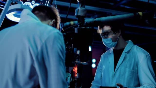 vídeos y material grabado en eventos de stock de jóvenes científicos que buscan un experimento. los hombres usan bata blanca y vasos. laboratorio técnico. - autopsia
