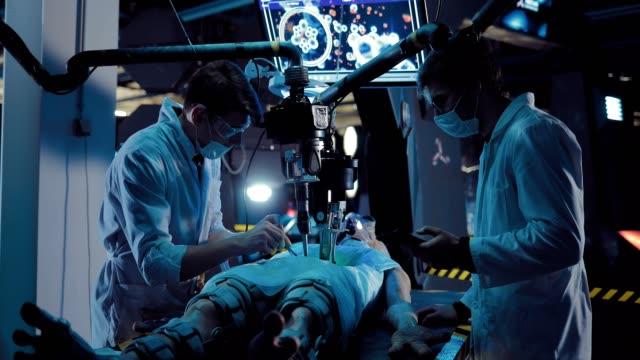 vídeos y material grabado en eventos de stock de los científicos jóvenes cirujanos realizan experiencia científica en el extranjero. los asistentes de laboratorio hacen una autopsia de un extraterrestre espacial con la ayuda de equipos y herramientas. - autopsia