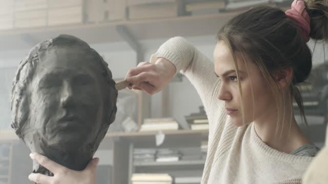 giovane scultore crea una scultura in argilla - professione creativa video stock e b–roll