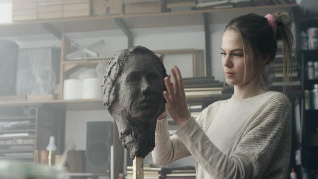 giovane scultore crea una scultura in argilla - scultura video stock e b–roll