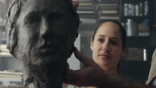 Young sculptor creates a clay sculpture video