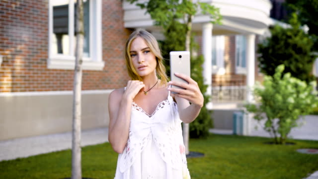 Young sensual girl in white taking selfie while posing alone at summer street video