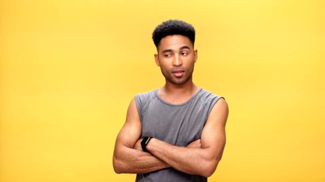 Young serious african man with arms crossed over yellow background. video