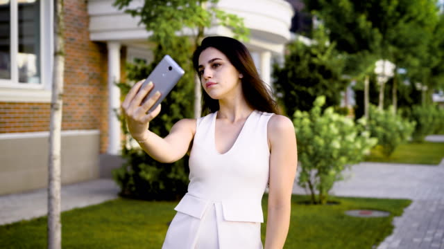 Young serious brunette in white dress posing for selfie holding smartphone on street background video