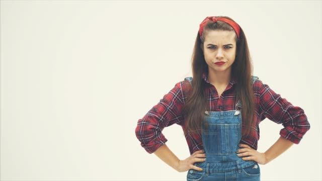Young serious frowning girl standing, her hands akimbo, then wagging her finger, threatening. Pin-up style. 4K video of attractive girl isolated on the white background. Copy space. arms akimbo stock videos & royalty-free footage