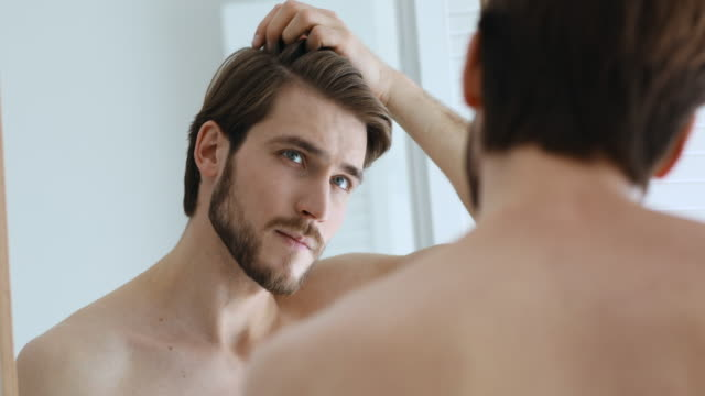 Young serious handsome european man assessing hair condition. Young serious handsome european man looking at mirror, combing styling hair with fingers, assessing hair condition, worrying about dandruff or thinking of visiting barbershop and haircut service. human hair stock videos & royalty-free footage