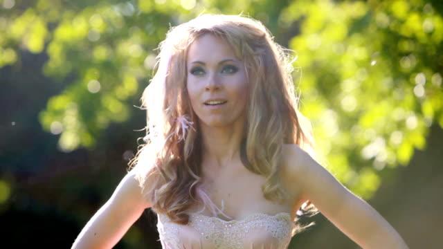 giovane sexy biondo ragazza in abito rosa elegante danza nel bosco - sfilata video stock e b–roll