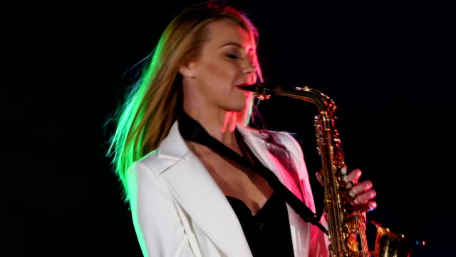 Young Sexy Blonde Woman Dj In White Jacket Playing Music Using Saxophone On Black