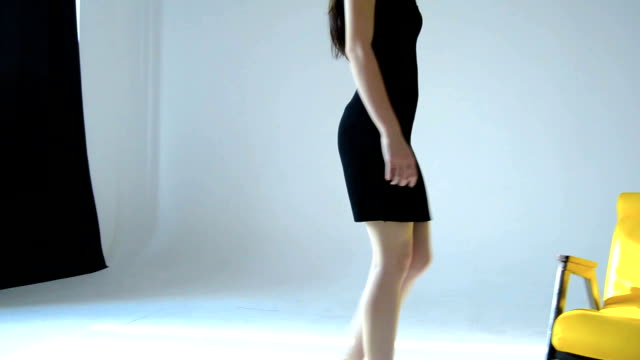 young Sexy brunette in black dress goes to the Studio and sits on a Chair video