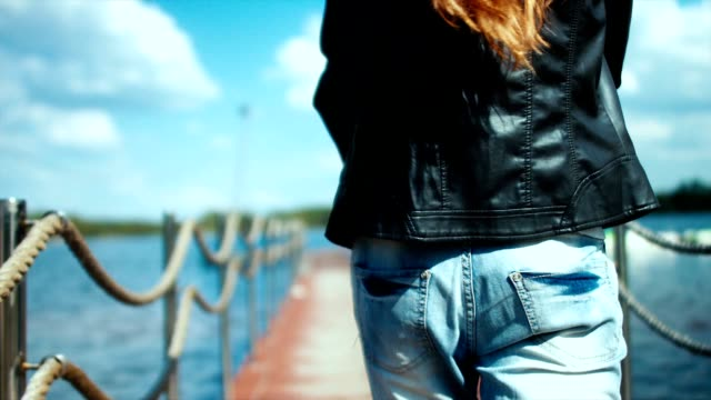 Young sexy Caucasian girl walking on a pier with boats video