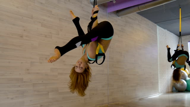Young sexy girl doing stretching, hanging upside down in the gym. Young sexy girl doing stretching, hanging upside down in the gym. This aerobics is an effective tool for stretching muscles, normalization stimulation of biological processes and the organism as a whole. leotard stock videos & royalty-free footage