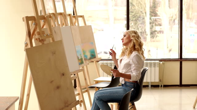 a young sexy girl in a white shirt draws on canvas in the studio for drawing. - cavalletto attrezzatura per arti e mestieri video stock e b–roll