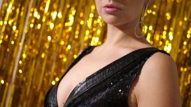 Video young sexy girl in black dress of scales stands on the background of gold tinsel