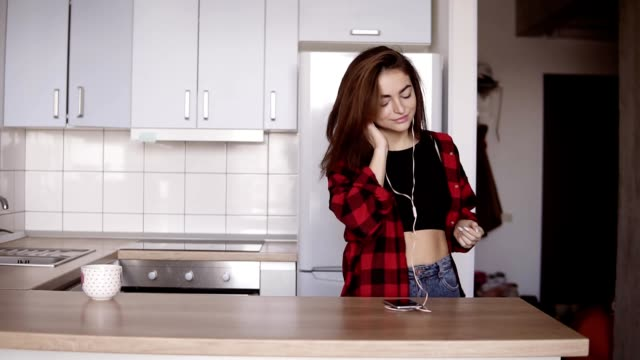 Young sexy girl in her 20's dancing in the kitchen with headphones in her ears, takes a cup from the table. video