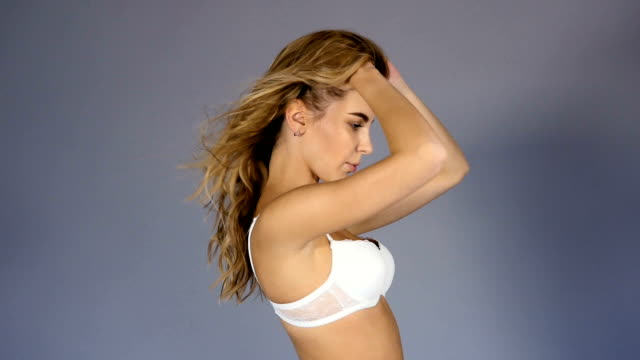 chica joven sexy con el pelo largo en blanco ropa interior posando - vídeo