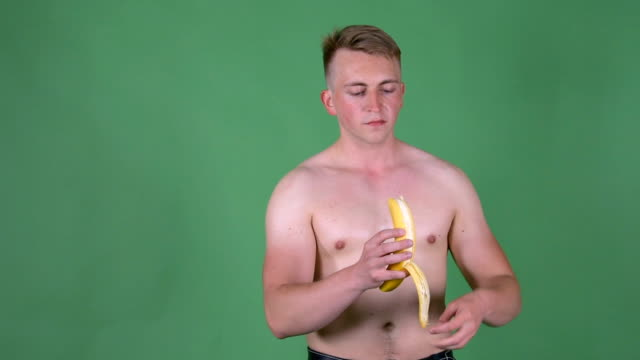 A young sexy guy is eating a banana.