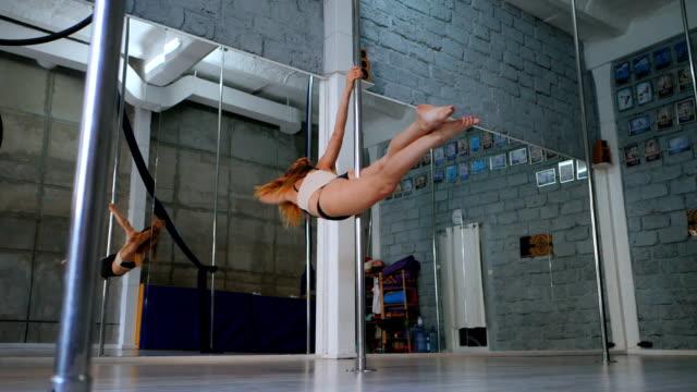 jung sexy schlanke frau pole dance in grauem interieur. schöne, attraktive mädchen pol tanz. lady mit guter figur tanzen am pylon. slow-motion - sportliga stock-videos und b-roll-filmmaterial