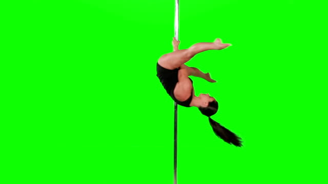 Young sexy woman exercise pole dance against a green screen video