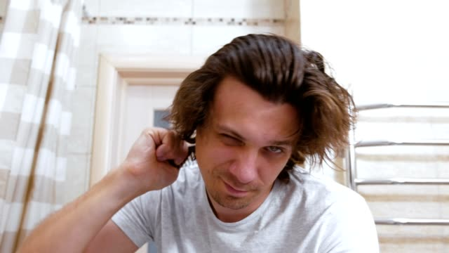 young shaggy man combs hair with a comb after head washing. - pelo animale video stock e b–roll