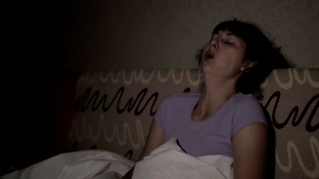 Young sick woman coughs at home night on the couch. The girl suffers from a cough and holding tissue ,flu symptoms. Healthcare and medical concept. Colds are the flu infection. Asthma attack. video