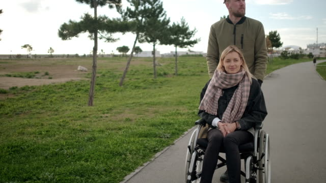 Young sick woman is sitting in wheelchair, man is helping her and rolling Cheerful blonde woman is resting in medicine carriage and her husband is pushing it. Pair of spouses is walking together in park pushing wheelchair stock videos & royalty-free footage