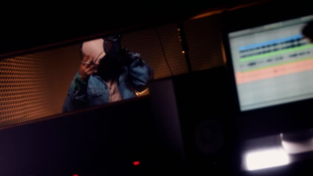 Young singer and music producer recording songs at music studio