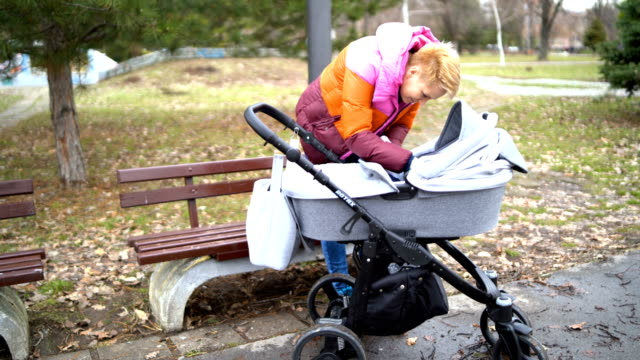 Young single mother, in a park with her son, a boy, in a wheelchair, looks after, cares. A happy family. Walking in the open air. Mother's Day, children's protection. A small child on a walk.