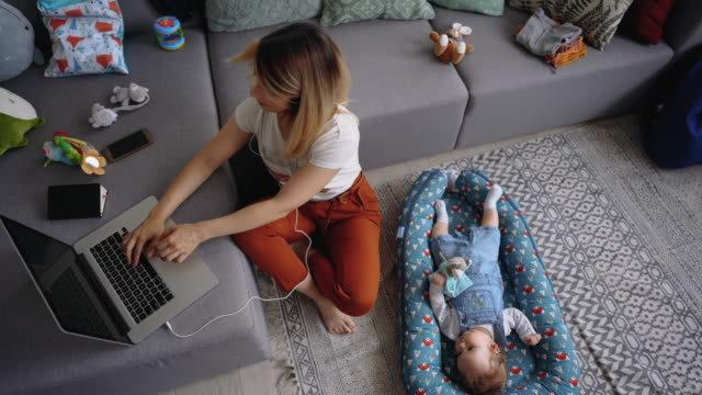 Young single mother working from home with her baby boy laying next to her video