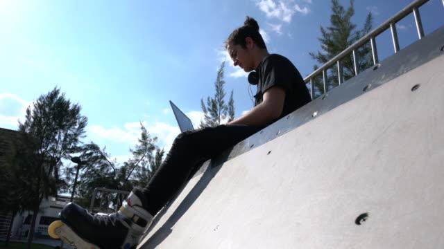 青空の下で座っている若いスケーター - スケートボードをする点の映像素材/bロール