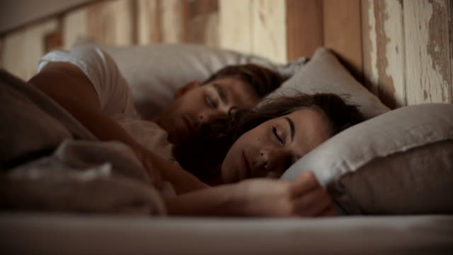 Young sleeping couple in bed video