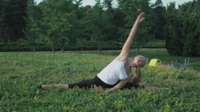 Young slender blonde in shirt performs exercise incline on the hill with green grass in the park video