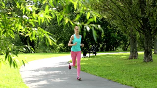 young slender woman jogging in a city park. dolly shot. - tävlingsdistans bildbanksvideor och videomaterial från bakom kulisserna