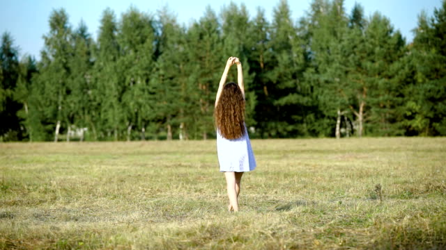 young slim brown-haired woman is strolling in field near green forest in summer day, back view video
