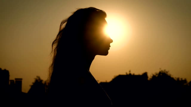young slim woman with long wavy hair is walking in evening time in countryside, close-up portrait against the sun