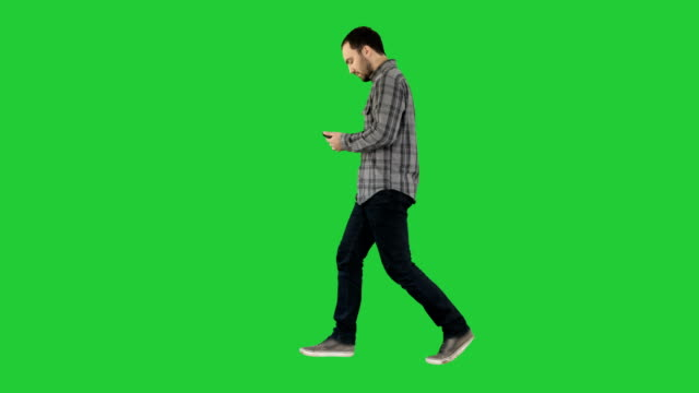 Video Young smart casual man walking and reading message on cell phone on a Green Screen, Chroma Key