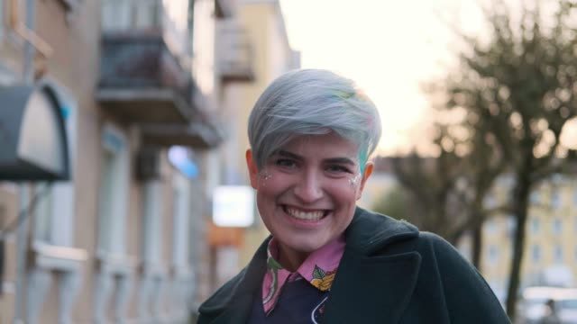 A young smart woman with a short haircut and dyed colored hair, in a green coat and a sweater with prints on the street of the city. A young smart woman with a short haircut and dyed colored hair, in a green coat and a sweater with prints on the street of the city. Fashionable informal girl. blue hair stock videos & royalty-free footage