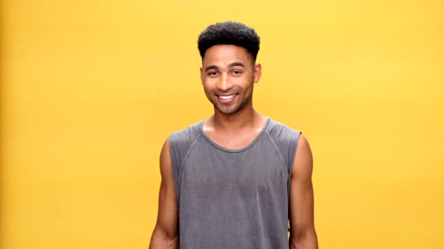 Young smiling african man posing over yellow background. video
