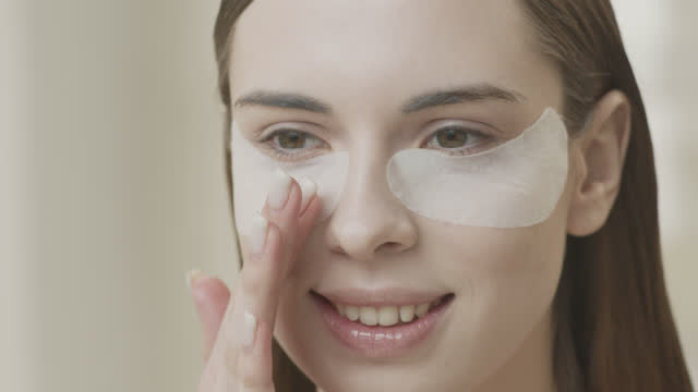 Young smiling and joyful girl makes cosmetic procedures for the face in the morning. video