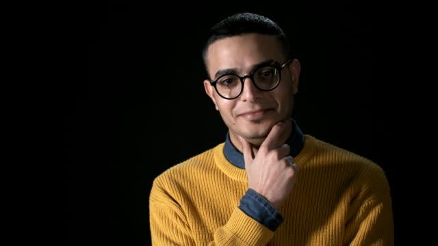 vídeos y material grabado en eventos de stock de joven hombre árabe sonriente sobre fondo negro - un solo hombre