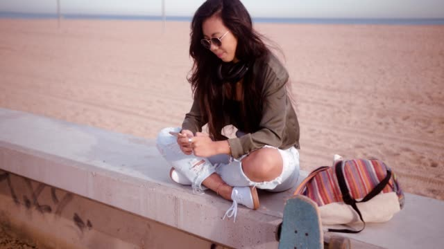vídeos de stock e filmes b-roll de young smiling asian skater girl having fun texting at beach - etnia filipina