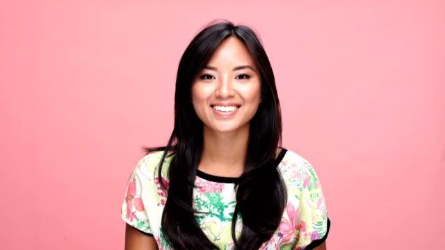 vídeos de stock e filmes b-roll de young smiling asian woman wink over pink background. - piscar