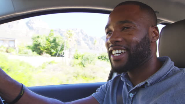 young smiling black man driving car on a road trip - driver stock videos and b-roll footage