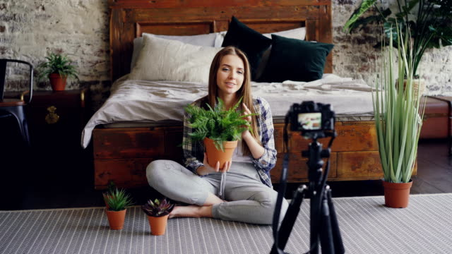 Young smiling blogger in casual clothing is holding flowers, talking and recording video blog for online vlog about house plants using camera on tripod. video