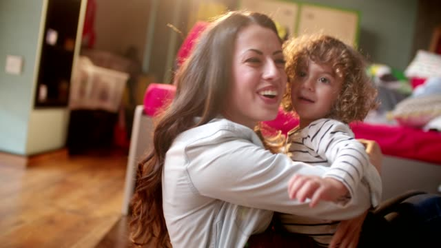 Young smiling brunette mother embracing her cute blond son Young beautiful brunette aunt cheerfully hugging her blond nephew while playing together playroom stock videos & royalty-free footage