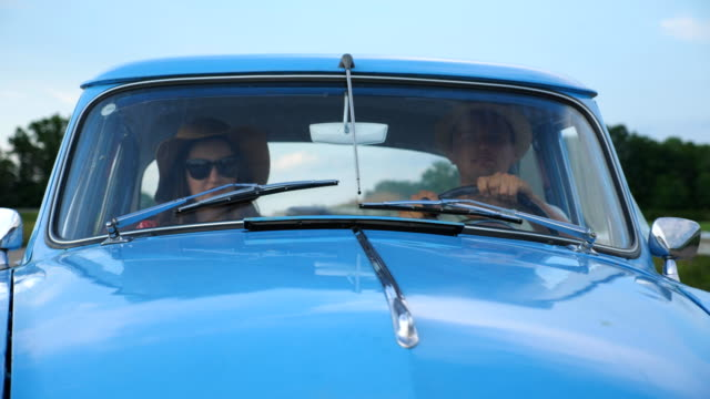 Young smiling couple in hats riding at vintage car during summer travel. Happy man and woman sitting at the front seat of old retro car and enjoying ride and holidays. Road trip concept. Slow motion