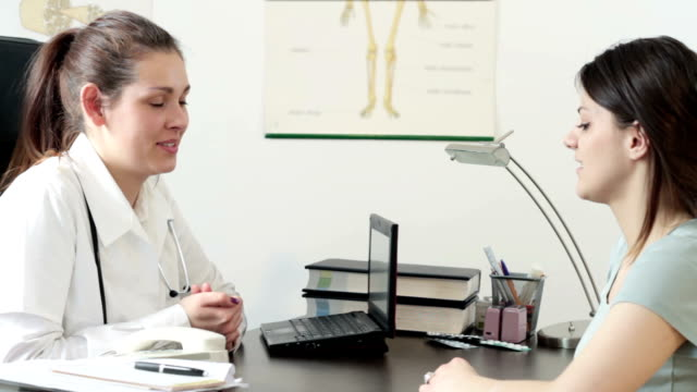 Young smiling doctor talking to her female patient at office video